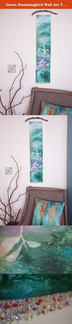 """Green Hummingbird Wall Art Tapestry. Misty nature silhouettes float over vibrant, watercolor hues in this unique hanging Art Panel. It is hand painted using a textile pigment on silky fabric, resulting in a subtle texture and shimmer. It measures about 8"""" x 36"""", a long, narrow painting perfect for small spaces. Delicate loops of ribbon allow it to be hung on a decorative rod or branch, while beaded fringe at the bottom adds a bit of sparkle and weight for a nice drape. Each Art Panel is..."""