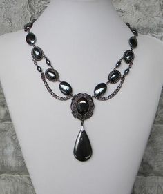 A one of a kind hematite gray jewelry necklace, dark with an ornately detailed center focal holding a large rhinestone, smooth flat ovals are in gunmetal setting links, and earrings are included, $72.00 https://ericascreativecavalcade.com/products/lovely-lady-in-gray-ericas-creative-cavalcade