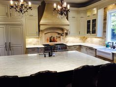 French Country Kitchen Taj Mahal Quartzite  countertops with marble backsplash(light empador). I love the cream Wellborn cabinets. Wolf and Subzero. The Tuscan hood is perfect!