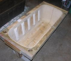 "Pete added curved pieces cut from PVC pipe to the interior to create decorative detail on the exterior of the trough. Automotive ""bondo"" was applied to the interior of the mold to smooth the surfaces and hide the screw heads and grooves in the plywood. Once the bondo set and was sanded smooth, the mold was sawn in half to allow the hypertufa pot to be removed."