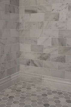 Large gray and white marble subway tile on shower wall and baseboard with a hexagon pattern on the floor.?