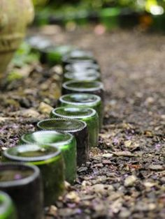 Upturned bottles edge garden path. I saw this done at the old Alley Cat Cafe- they also used them along the path buried up to the bottom so just the round bottom showed- very cool!
