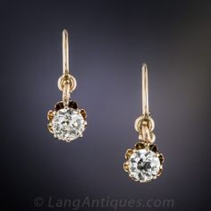 A beautiful pair of bright white old mine-cut diamonds, together weighing .85 carat, dance and dazzle from within freely swinging 14K rose gold buttercup settings. Circa 1900. Perfect for everyday or any day.