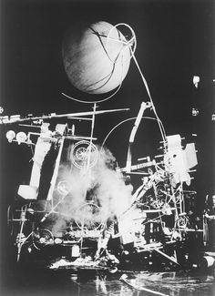 Jean Tinguely - Homage to New York (1960)    Jean Tinguely was asked in 1960 to produce a work to be performed in the Sculpture Garden of the Museum of Modern Art in New York. In collaboration with other artists/engineers, among them Billy Klüver and Robert Rauschenberg, he produced a self-destroying mechanism that performed for 27 minutes during a public performance for invited guests. In the end, the public browsed the remnants of the machine for souvenirs to take home.
