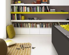 Pour dynamiser une peinture salon blanc, un mur est peint couleur taupe et du jaune moutarde pour les objets déco et ainsi  donner du relief...