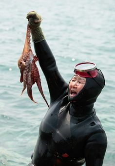 """I GOT IT!"" A jubilant Haenyeo (Jeju diving woman) proudly raises her catch at the 5th annual Haenyeo Diving Festival on Jeju Island, Korea"