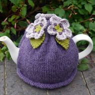 Made with dusky shades of mauve and purple, this hand knitted tea cosy will look beautiful on the breakfast table.  It has three crocheted flowers attached. Made with lovely soft wool which will keep the teapot nice and warm. Will fit a standard 4 - 6 ...