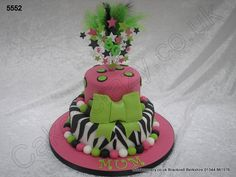 A bright coloured two tier birthday cake in pink white and lime green. The lower tier in zebra style icing stripes and the upper tier black and green polka dots. Large sugar balls and bow around the sides and topped with a lime green starburst topper