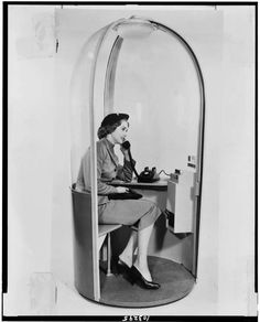 Woman inside modern telephone booth, 1958