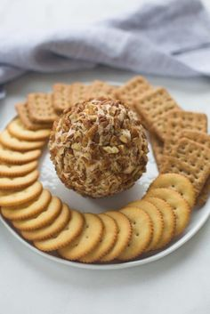 A round plate with a cheese ball (covered in crushed nuts) in the center and crackers fanned in a circle around the edge of the plate.