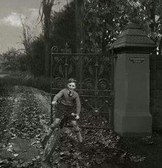 A Young John Lennon at the gate of Strawberry Field.