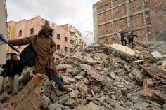 A resident of the village of Imzouren, near Al Hoceima, steps over rubble a day after an earthquake, measuring 6.3 on the open-ended Richter scale, hit the region in 2004