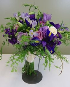 A victorian clutch bouquet of lavender, purple and green featuring lisianthus, iris, roses, freesia, stock, trichelium, hypericum, maiden hair fern and ivy.