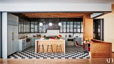 The kitchen features pendant lights by the Lamp Goods, a Wolf microwave, Lostine stools, and a checkerboard concrete-tile floor; Ashe + Leandro designed the cabinetry and hood.