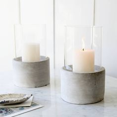 Simple candle holder for all seasons.Substantial clear glass container rests on a circular smooth concrete base with protective rubber pads underneath making an on trend utilitarian design. Perfect for candle light in the home or for seasonal garden table dining. Available to purchase with the off white pillar candle featured. Sold as a single candle holder.Glass, concrete14cm Dia x 23cm H