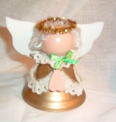 Here is a cute little angel to sit upon your shelf. Its body is made from a gold-colored metal bell (no clapper). It has curly blond hair, and