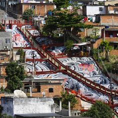 """This intricate, painted river in Rio was once ugly concrete. Street artists Haas & Hahn created the Japanese-style design featuring koi carp swimming upstream, with help from the local community and tattoo artist Rob Admiraal. The project took almost a year to complete, and the artists came to love their temporary neighbors. """"All the time we spent in the neighborhood was maybe even more important than the painting itself,"""" Haas & Hahn said in their #TEDTalk."""