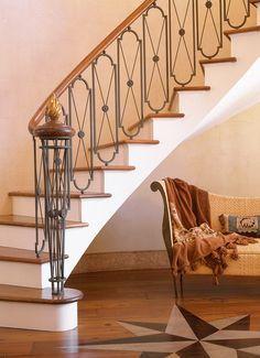 The unusual balusters in the foyer staircase are individual welded-metal elements that pivot at top and bottom so that they can be turned to follow the curve of the stairway.The Work of Architect Ken Tate.