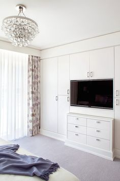 Stunning bedroom with wall of built-in closets framing built-in flatscreen TV over built-in dresser across from bed illuminated by Robert Abbey Bling Chandelier.
