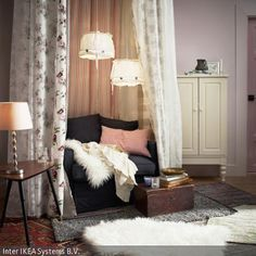 Umrahmt von einen Schleier aus feinen Stoffen und Gardinen wurde das Sofa wie ein Himmelbett gestaltet. Innerhalb der gestreiften Gardinen und der Gardinen mit Blumenmuster …