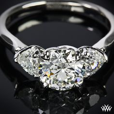 In LOVE - This Custom 3 Stone Diamond Engagement Ring is set in platinum and features a W-Prong design. The 1.30ct Expert Selection center diamond is flanked with 2 Heart Cut Diamond side stones (0.40ctw).