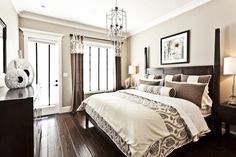 Dark wood floor bed and drapes contrasts with neutral walls and bedding.