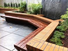 Back yard courtyard with water feature, brick planters, and floating ipe bench creates an inviting place to entertain