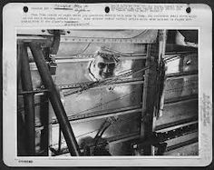 Louie Zamperini peering through a hole made by a 20mm cannon shell. Note the emergency splice in the rudder control cables. It was done by Zamperini while in-flight back to Funafuti Island after the April 18,1943 mission to Nauru. The plane had almost 600 holes in it when it landed and all the enlisted gunners were wounded, one succumbing to his wounds later that night (T/Sgt. Harold Brooks - Waist Gunner/Radio Operator).