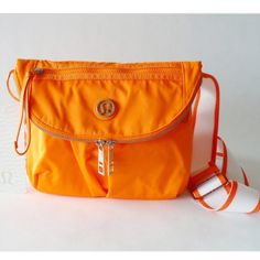 "Lululemon orange festival bag. Good condition! Has been sitting in my closet as I rarely use anymore because I bought another one! The fabric is repellent! It can be worn as a cross body or fanny pack around the waist. 9"" by 5"" by 11"". They no longer make this color. These are stock photos I can post photos of exact bag if needed! lululemon athletica Bags Crossbody Bags"