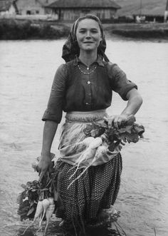 Girl farm worker washing turnips in the river on a collective farm. Photograph by Paul Schutzer. Romania, 1963