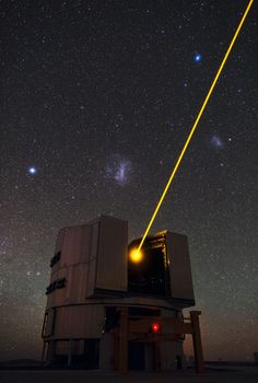 Telescope shoots yellow laser into the sky to create a glowing spot in the Earth's atmosphere to control the telescope's deformable mirrors and remove the effects of atmospheric distortions, producing images almost as sharp as if the telescope were in space. The image also captures the Large and Small Magellanic Clouds, nearby irregular dwarf galaxies, to the left and to the right of the laser beam, respectively.  http://www.space.com/34-image-day.html