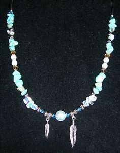 Custom order necklace...turquoise, moonstone, glass pearls, blue and amber crystals, silver-tone beads, a glass disc, and silver-tone feathers.