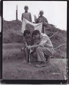 An (American?) man gives a liberated Japanese comfort women first aid as two Chinese Nationalist soldiers stand behind him, displaying a captured Japanese flag.