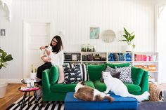 Katie and her three cats in the living room of the Queensland, Australia house she's owned for seven months. She shares the space with her partner.