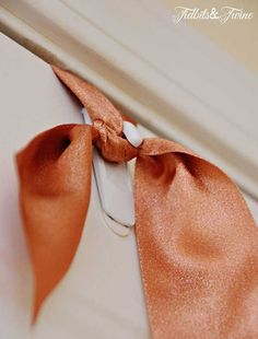 Hang your wreaths with soft ribbon and a command hook. Less damaging to door than a metal wreath hanger and much quieter!