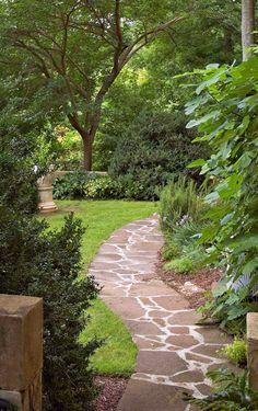 Garden Path A stone pathway winds around the home's rear facade.