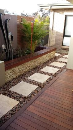 "ESTO CON LAS ""CINTA"" DE 4in DE ANCHO DE PIEDRAS BLANCAS. PARA LOS COSTADOS DE LA CASA. Large white paving stones with dark rock or crushed gravel. Bench on the other side."