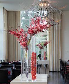 Tall vase arrangement of red branches by Ken Marten.