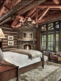The master bedroom of a luxury mountain home by Miller Architects PC. Crossed wooden beams blend with locally obtained logs. A stone fireplace is nestled neatly next to ceiling high windows, offering patrons a glorious view. http://ctmarchitects.com/