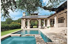 Architect Edward B. Frierson and home builder Frederick Fuentes created this covered porch which houses an outdoor fireplace and living and dining areas.