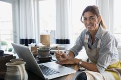 Portrait smiling woman with pottery at laptop