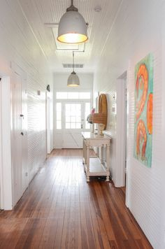 The best part about wainscoting coated in fresh white BEHR paint? Your unique decor pieces, like statement artwork, are showcased wonderfully—and your space will have tons of light! White Wood Floors, Wood Flooring, Cottage Lighting, Seaside Style, Exposed Wood, Seaside Towns, Adventure Awaits, Beach Themes, Home Projects
