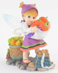 This stone resin figurine features the Autumn Bounty Fairie, she is carrying pumpkins and grapes in her apron and has baskets of pears and potatoes sitting around her.