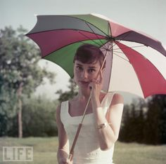 Audrey Hepburn wears a sundress and holds a colorful umbrella in 1955.