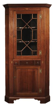 Southern Federal Inlaid Cherry Corner Cupboard possibly Kentucky, 19th century in part, single-case construction, cherry with poplar secondary, glazed door opening to two fixed interior shelves with scalloped fronts over dovetailed drawer flanked by two false drawer fronts over a paneled door, fan, bellflower and urn inlays, shelved interior, bracket feet, 82-1/2 x 38-1/2 x 21 in