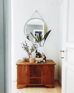 circle mirror hung over vintage short wood dresser. / sfgirlbybay