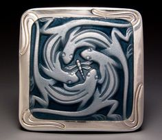 By Michele Raney.  Love this piece.  I love the way the Salamanders tails flow into the silver framing this piece.  This woman is truly an artist.