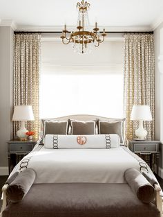 Big open window, white lamps, grey furniture, small chandelier and monogrammed bedding