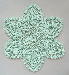 This newly-crocheted thread doily has six pineapple motifs and measures about 12 inches across. It was crafted with a steel hook and 10# cotton thread in mint green. This pattern is from the 1946 Coats and Clark's crochet book Pineapple Designs. It's the bread-and-butter doily from the pineapple place settings. Center is crocheted in the round while pineapple tips are crocheted separately. Lovely for Victorian or traditional decor. Can also be used as a motif for embellishments.