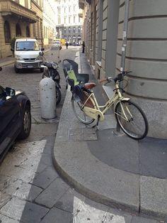 Gli automobilisti parcheggiano spesso male. I ciclisti peggio. Notare che l'auto è sulle striscema in una strada chiusa e ha preso la multa. La bici legata al palo che blocca il marciapiede no. Mah! Da via Rovello 1 Milano da Vedere